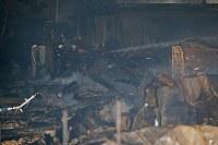 焼け落ちた民家や商店に向かって放水する消防関係者ら=新潟県糸魚川市で2016年12月22日午後7時27分、小川昌宏撮影
