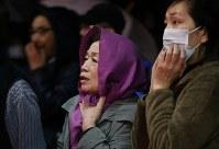 燃えさかる炎を不安そうに見つめる人たち=新潟県糸魚川市で2016年12月22日午後8時7分、小川昌宏撮影