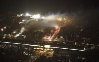 煙を上げ続ける市街地。手前はJR糸魚川駅=新潟県糸魚川市で2016年12月22日午後9時2分、本社機「希望」から丸山博撮影