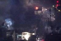 煙を上げ続ける市街地=新潟県糸魚川市で2016年12月22日午後9時3分、本社機「希望」から丸山博撮影