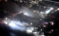 煙を上げ続ける市街地。奥はJR糸魚川駅=新潟県糸魚川市で2016年12月22日午後8時51分、本社機「希望」から丸山博撮影