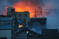 Firefighters work to extinguish flames from the roof of a structure in Itoigawa, Niigata Prefecture, on the afternoon of Dec. 22, 2016. (Mainichi)