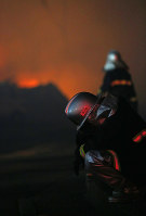 A firefighter appears exhausted after battling a blaze that broke out in Itoigawa, Niigata Prefecture, shortly after 5:30 p.m. on Dec. 22, 2016. (Mainichi)