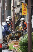 Niigata Prefectural Police officers and firefighters on Dec. 23, 2016, carry out a burnt table from the ramen shop where a blaze that swept through downtown Itoigawa, Niigata Prefecture, started the previous day. (Mainichi)