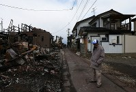 Two districts separated by a narrow alley, one that burned down in a massive fire and the other that survived, are seen in Itoigawa, Niigata Prefecture, on Dec. 25, 2016. (Mainichi)