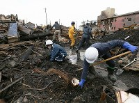 Volunteer workers dig through debris in downtown Itoigawa, Niigata Prefecture, on Dec. 25, 2016. (Mainichi)