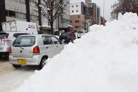 大雪の影響で幅が狭くなり、混雑する道路=札幌市中央区で