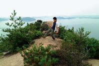 石島(岡山・香川) 海を挟んだ2県じゃなかった? 瀬戸内海に浮かぶ石島は、岡山県と香川県の県境が島内を横切っている。海にはさまれた2県を歩いて行き来できる小さな島だ。香川県では井島という。北部は岡山県玉野市、南部が香川県直島町だが、島の西端100メートルほどには県境がない。江戸時代に漁場をめぐる争いがあり、幕府が下した裁定が今の県境になった。現在も漁業権の問題があり、そのままの状態になっている。