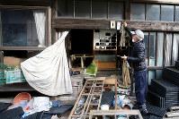 イノシシなどが荒らした自宅の軒先にしめ飾りを掛ける鈴木久友さん。「普通ならミカンとか餅とか付けるけど、食べられちゃうから」と話した=福島県大熊町で2016年12月26日、森田剛史撮影