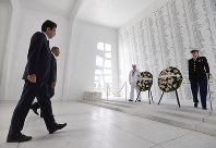 Japanese Prime Minister Shinzo Abe, left, and U.S. President Barack Obama walk toward wreaths placed in front of a wall listing the victims of the Pearl Harbor attack, at the USS Arizona Memorial off the island of Oahu in Hawaii on Dec. 27, 2016. (Mainichi)
