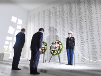 Japanese Prime Minister Shinzo Abe, foreground right, and U.S. President Barack Obama, left, observe a moment of silence in front of a wall bearing the names of Pearl Harbor attack victims, at the USS Arizona Memorial in Oahu, Hawaii, on the morning of Dec. 27, 2016. (Mainichi)