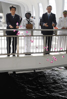 Prime Minister Shinzo Abe, left, and President Barack Obama, second from right, sprinkle flower petals into the ocean at Pearl Harbor where the USS Arizona was sunk, off the island of Oahu in Hawaii on Dec. 27, 2016. (Mainichi)