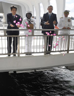 Japanese Prime Minister Shinzo Abe, far left, and U.S. President Barack Obama, second from right, throw petals into the ocean at Pearl Harbor where the hull of the USS Arizona lies, in Oahu, Hawaii, on the morning of Dec. 27, 2016. (Mainichi)