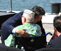 Prime Minister Shinzo Abe hugs a former U.S. serviceman who survived the attack on Pearl Harbor, after finishing his speech, at Pearl Harbor in Hawaii on Dec. 27, 2016. (Pool photo)