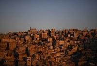 夕日に染まるアンマンの旧市街。いくつもの丘が連なり、傾斜のきつい坂道が多い。こうした高台や中心部から離れた郊外は家賃が安く、多くのシリア難民が暮らしている=ヨルダン・アンマンで2016年9月20日、久保玲撮影