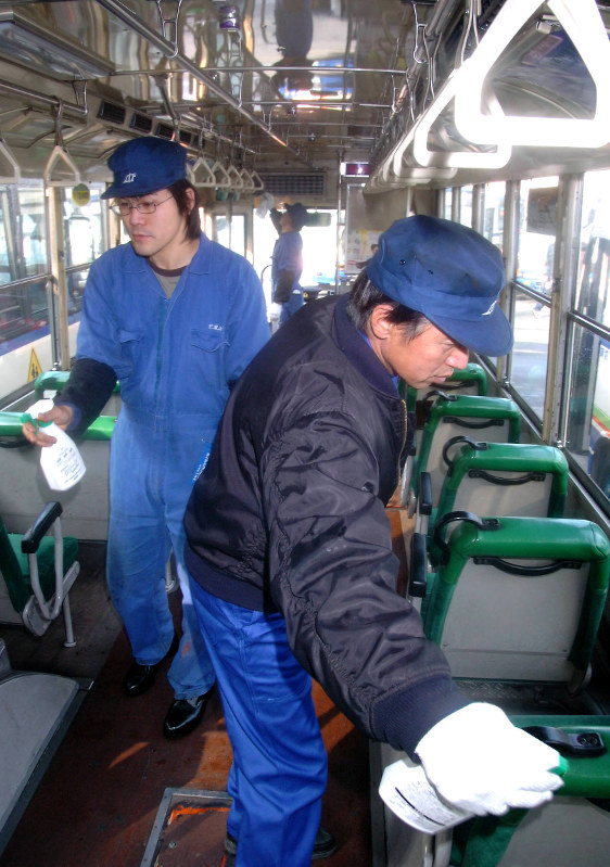 ノロウイルス感染を予防するため、バスのつり革や座席を消毒する整備士=広島県福山市で2007年1月18日、茶谷亮撮影