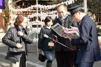 特殊詐欺被害の防止を呼び掛けるチラシを受け取る参拝客たち=松山市御幸1の県護国神社で、木島諒子撮影