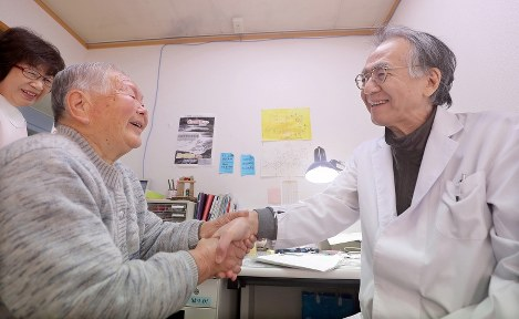 「だぶが崩れそう(涙が出そう)」。そう言って近江医師の手を握る村上キクミさん(92)。診療所に来て近江医師とおしゃべりすることが楽しみだった村上さんは「何を支えにしたらいいの」と言葉を詰まらせた=岩手県陸前高田市で2016年12月19日、喜屋武真之介撮影