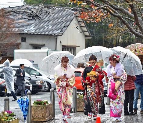 熊本地震による倒壊家屋(左後方)が残る中、成人式の会場に向かう晴れ着姿の新成人たち=熊本県益城町で2017年1月8日午前9時49分、野田武撮影