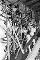 足場に上って壁画を制作する女性たち。当時の週刊文春がグラビアで掲載した(文藝春秋提供)