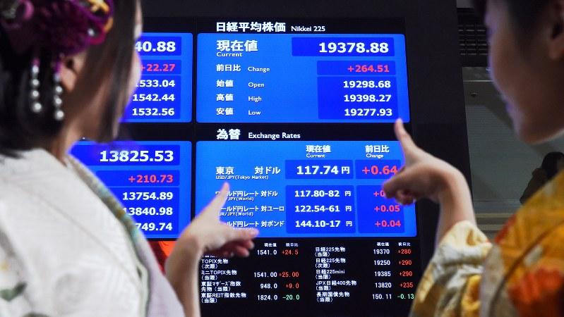 東京証券取引所の大発会に晴れ着姿で参加した女性と、年初の日経平均株価等の動きを示すボード=2017年1月4日、竹内紀臣撮影