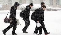 Exam takers in Akita are seen walking through the snow on their way to unified university entrance exams, on the morning of Jan. 14, 2017. (Mainichi)