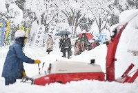 A worker is seen clearing snow as exam takers, rear, are seen heading to unified university entrance exams in Nagaoka, Niigata Prefecture, on the morning of Jan. 14, 2017. (Mainichi)