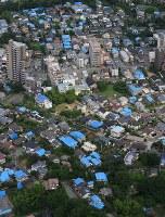 屋根にブルーシートをかぶせた家が並ぶ熊本地震の被災地。住宅被害の8割は一部損壊だった=熊本市で2016年6月、本社ヘリから山下恭二撮影