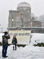 A family takes a commemorative photo in front of the snow-covered Atomic Bomb Dome in Hiroshima's Naka Ward on Jan. 15, 2017. (Mainichi)