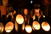 阪神大震災の発生時刻に犠牲者の冥福を祈り、手を合わせる人たち=神戸市中央区の東遊園地で2017年1月17日午前5時46分、加古信志撮影
