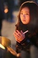 竹灯籠の灯りを見つめながら手を合わせる女性=神戸市中央区の東遊園地で2017年1月17日午前6時45分、幾島健太郎撮影