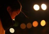 竹灯籠を見つめる女の子=神戸市中央区の東遊園地で2017年1月17日午前6時16分、久保玲撮影