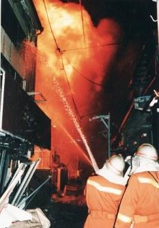震災直後に燃え上がった家屋に放水する消防隊員=神戸市内で