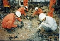 火災で焼け野原となった住居跡で遺骨を探す隊員ら=神戸市内で