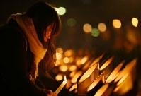竹灯籠を見つめる平島智恵さん(37)。「姉弟みたいに仲が良かった」という当時4歳の親戚の男の子を亡くした。東遊園地には毎年訪れる。「また新しい一年をこの場所からスタートできる」=神戸市中央区の東遊園地で2017年1月17日午前6時11分、久保玲撮影