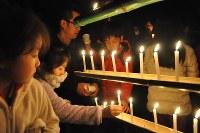 阪神大震災後に避難所となった本山第一小には約200人が集まり、ろうそくに火をともして犠牲者に黙とうをささげた=神戸市東灘区本山北町で2017年1月17日午前6時4分、五十嵐朋子撮影