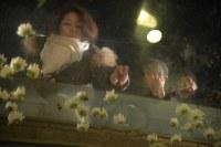 モニュメントに献花する女性たち=神戸市中央区の東遊園地で2017年1月17日午前6時23分、加古信志撮影