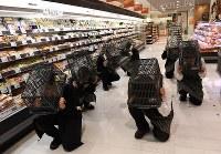 神戸市は巨大地震を想定した防災訓練「シェイクアウト訓練」を市内の学校や企業などで実施した。ダイエー神戸三宮店では従業員ら約50人が買い物かごを頭にかぶってしゃがみ込む退避行動を取った=神戸市中央区で2017年1月17日午前10時3分、久保玲撮影