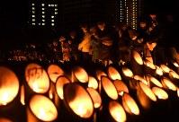 阪神大震災発生時刻に黙とうする人たち=神戸市中央区の東遊園地で2017年1月17日午前5時46分、久保玲撮影