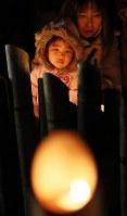 竹灯籠の明かりを見つめる親子=神戸市中央区の東遊園地で2017年1月17日午前5時35分、幾島健太郎撮影