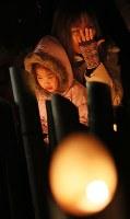 竹灯籠の前で涙ぐむ女性=神戸市中央区の東遊園地で2017年1月17日午前5時33分、幾島健太郎撮影