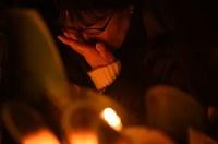 竹灯籠の前で目元を覆う女性=神戸市中央区の東遊園地で2017年1月17日午前5時47分、久保玲撮影