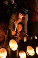 竹灯籠に火をともす人たち=神戸市中央区の東遊園地で2017年1月17日午前5時43分、加古信志撮影