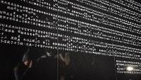 西宮震災記念碑公園の「西宮市犠牲者追悼之碑」に手を合わせる人たち=兵庫県西宮市で2017年1月17日午前5時50分、山崎一輝撮影