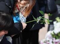 市立精道小学校で行われた阪神大震災の犠牲者の追悼式で、献花台に花を手向ける親子=兵庫県芦屋市で2017年1月17日午前10時29分、山崎一輝撮影
