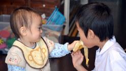 「お兄ちゃんも食べて」=東京都内で、関口純撮影