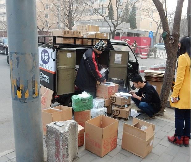 ネット通販の浸透で宅配需要が増す中、道端に荷下ろしされた荷物を、近隣住民が受け取りにくるスタイルも定着している=中国北京市内で1月17日、赤間清広撮影