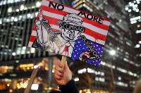 トランプ大統領の就任を前に、デモ行進する人のプラカード =東京都港区で2017年1月20日午後7時8分、小川昌宏撮影