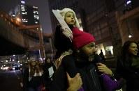 トランプ大統領の就任を前に、女性の権利などを訴えてデモ行進する大勢の人たち=東京都港区で2017年1月20日午後7時28分、小川昌宏撮影