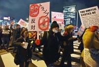 トランプ氏の大統領就任に反対し、デモ行進する人たち=大阪市北区で2017年1月20日午後7時44分、川平愛撮影